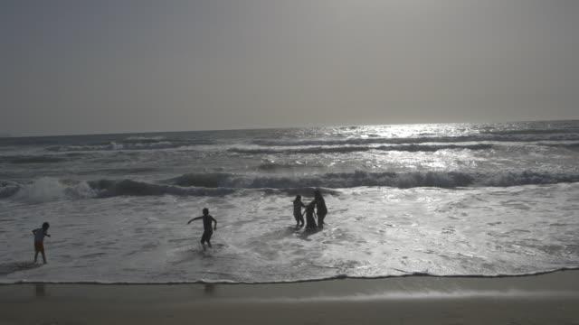 people wading in the ocean at tijuana beach, wide shot - tijuana stock videos & royalty-free footage