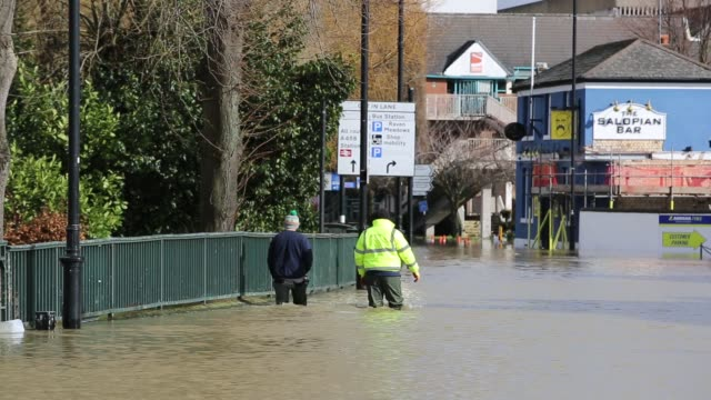 people wading through floodwaters in shrewsbury flooded by the river severn after the wettest february ever recorded in the uk febrary 2020 - walking in water stock videos & royalty-free footage