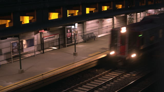 people wait as a metro north station in larchmont new york.  a train speeds through the station - bahnreisender stock-videos und b-roll-filmmaterial