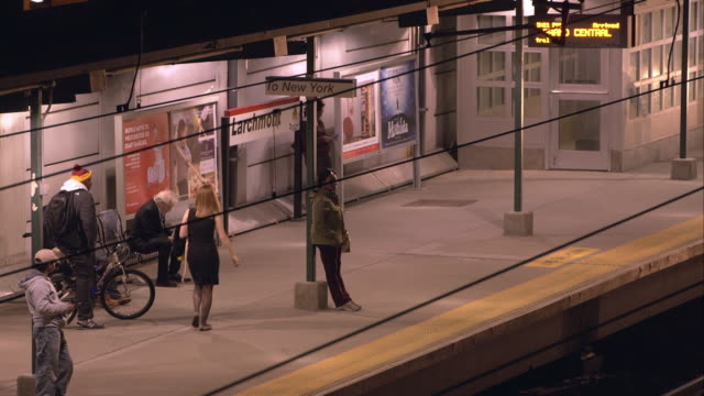 people wait as a metro north train arrives at the larchmont train station. - bahnreisender stock-videos und b-roll-filmmaterial