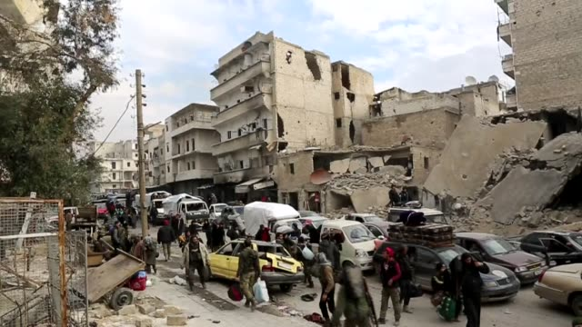 people wait at a crossing point at amiriyah district of aleppo, syria on december 16, 2016 to evacuate civilians, trying to flee from east aleppo... - evacuation stock videos & royalty-free footage