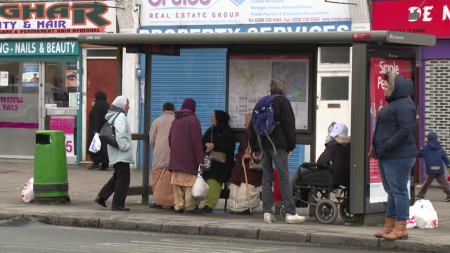 stockvideo's en b-roll-footage met people wait at a suburban bus stop on a grey day in burnt oak, greater london, uk. - informatiebord