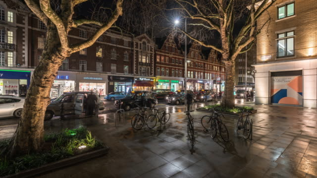 people wait for taxis to stop to pick them up as rapidly moving traffic flows along the kings road as lights from the shops reflect on the wet pavement and stationary bicycles stand on a pedestrianised area in the foreground - double decker bus stock videos & royalty-free footage