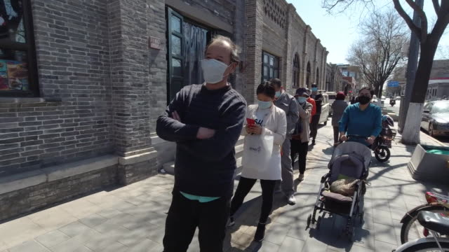people wait in a long queue outside of a food market in beijing during the covid19 pandemic - healthcare and medicine or illness or food and drink or fitness or exercise or wellbeing stock videos & royalty-free footage