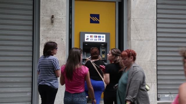 vidéos et rushes de people wait in line at an automated teller machine at a piraeus bank sa bank branch in athens greece on monday june 29 2015 shots an atm outside a... - athens greece