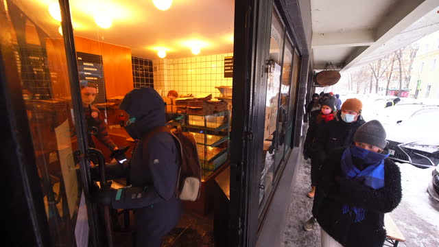 people wait in line at the miss mellow bakery on fat thursday in warsaw, poland on february 11, 2021. - 四旬節点の映像素材/bロール