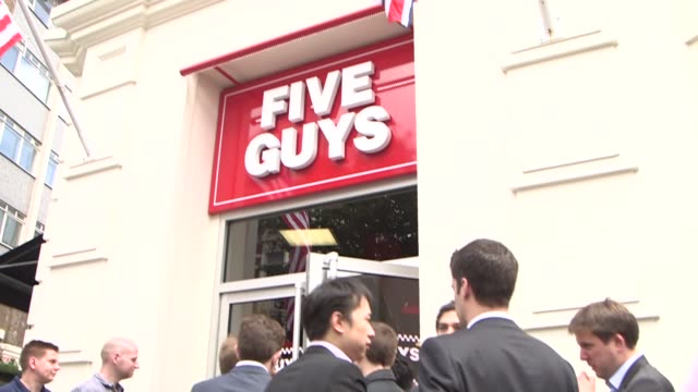 people wait in line for the opening of the first uk outlet of us burger restaurant chain five guys in covent garden london tilt down from signage to... - five people stock videos & royalty-free footage