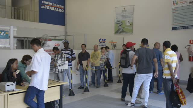 people wait in line to be served at cat centro de apoio ao trabalho sao paulo brazil on august 31st 2015 shots shots pan across a line of people... - trabalho no comércio stock videos & royalty-free footage