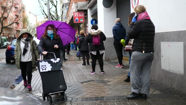 stockvideo's en b-roll-footage met people wait their turn in a queue to access a mercadona supermarket on march 17, 2020 in madrid, spain. supermarkets have applied stronger social... - number 9