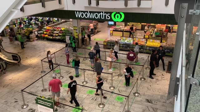 people wait to enter woolworths as the store uses social distancing cues to help create a safer environment for staff and customers during the... - social distancing stock videos & royalty-free footage