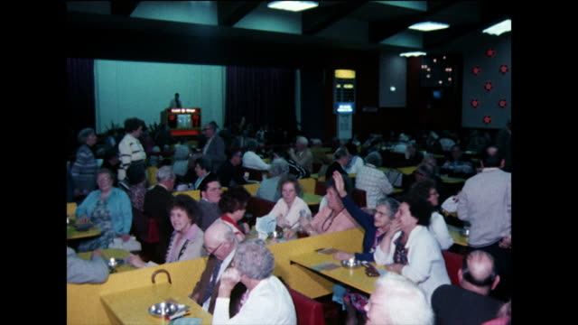 stockvideo's en b-roll-footage met people wait to play bingo in a crowded hall; 1978 - bingo