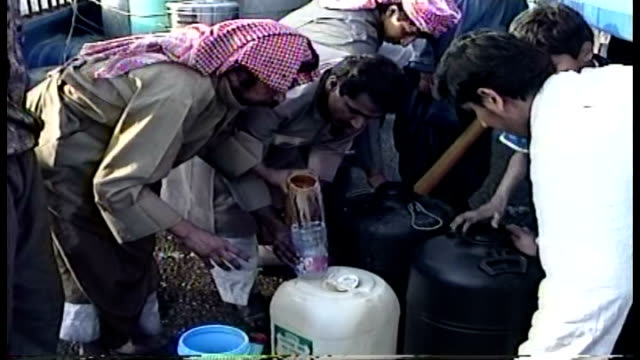 vidéos et rushes de people waiting as water pumped from tank on a truck into plastic containers using a water bottle as funnel - opération tempête du désert