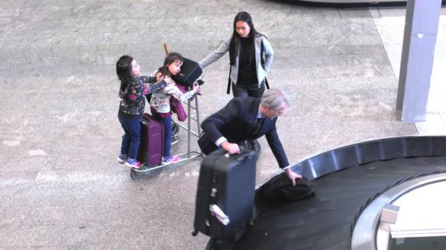 stockvideo's en b-roll-footage met mensen wachten voor bagage op de luchthaven terminal - oppakken