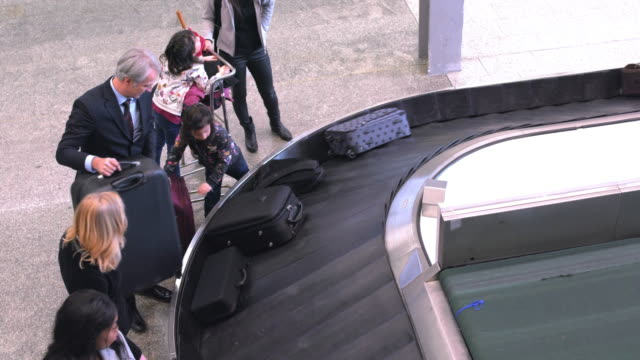 people waiting for baggage at airport terminal - baggage claim stock videos and b-roll footage