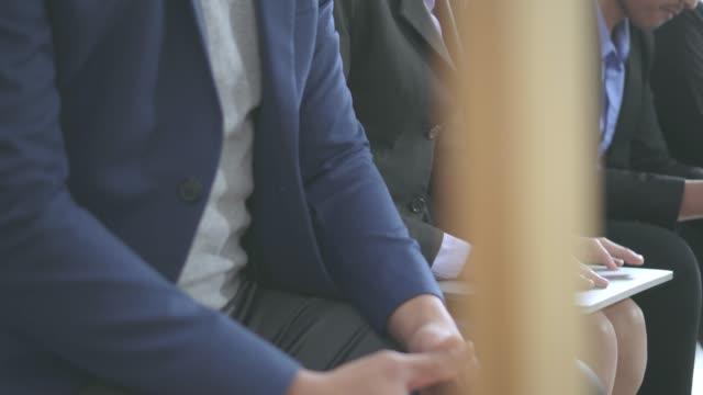 就職の面接を待っている人は、募集は退屈し、ガジェットを楽しみます。若い人たちは、椅子に座るインタビューを期待する - 立候補者点の映像素材/bロール