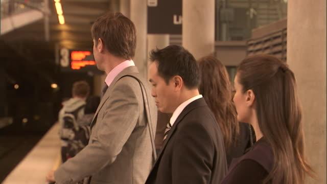cu, selective focus, people waiting for train, olympic park railway station, sydney, australia - せっかち点の映像素材/bロール