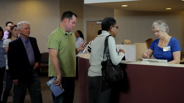ws people waiting in line at hospital reception desk / albany, new york, united states - ナースステーション点の映像素材/bロール