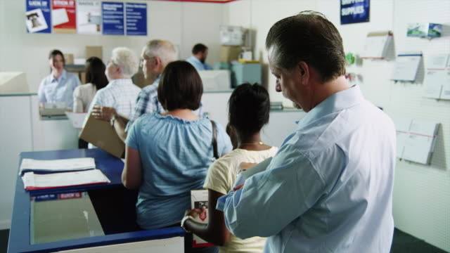 ms people waiting in line at post office / orem, utah, usa - postamt stock-videos und b-roll-filmmaterial