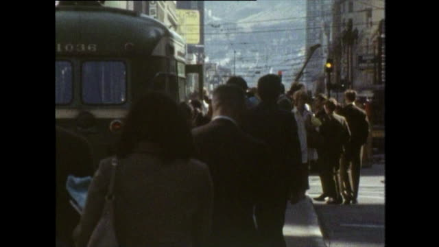 people waiting in line to board a bus in san francisco; 1970 - anno 1970 video stock e b–roll