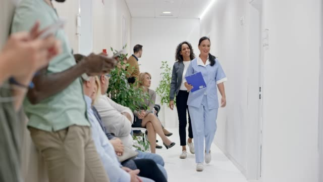 ds people waiting in the hallway of the clinic and the nurse calls a patient to go into the doctor's office - 50 59 years stock videos & royalty-free footage