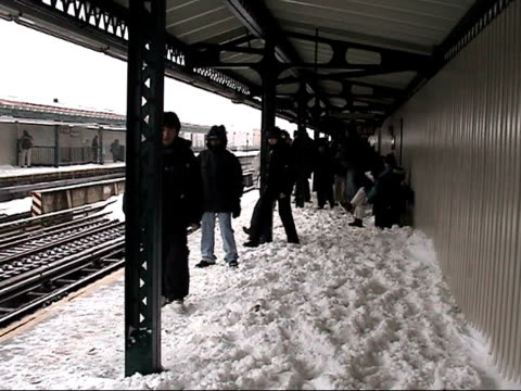 ms, people waiting on outdoor subway platform in snow, new york city, new york, usa - bahnreisender stock-videos und b-roll-filmmaterial