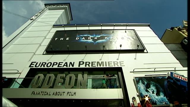 people waiting outside cinema man buying ticket at window wide shot of cinema exterior leicester square: odeon cinema with 'the dark knight' advert... - window box stock videos & royalty-free footage