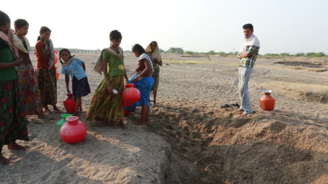 People waiting to get water out of an almost empty waterhole near Pannur, India