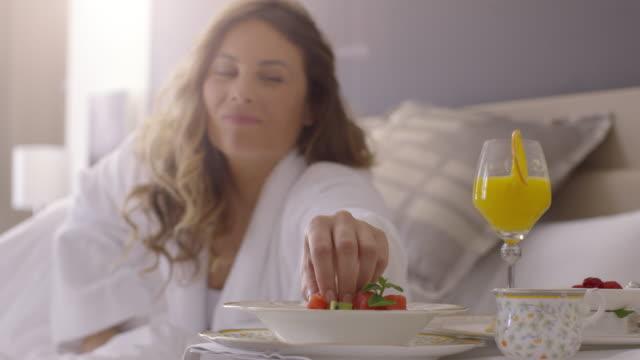 vidéos et rushes de gens se réveiller à l'hôtel. petit déjeuner au lit. - brightly lit