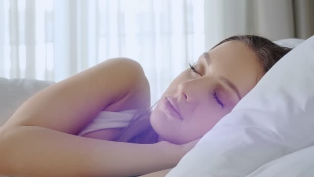 people waking up - young woman open her eyes on a sunny morning - adagiarsi video stock e b–roll