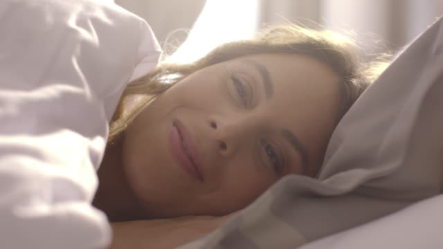 4K People waking up - Young woman opens her eyes on a sunny morning