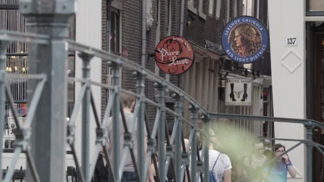 People walk across a bridge in Amsterdam