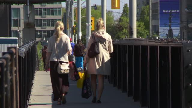 People walk across a pedestrian bridge in Toronto Canada.