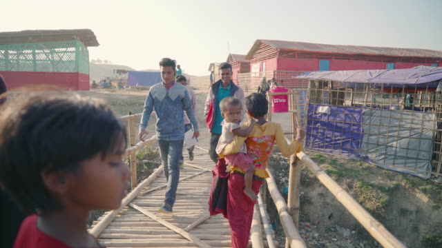 People walk across bridge through Kutupalong refugee camp in Bangladesh Bridges like this one litter the camps going over small bodies of water that...