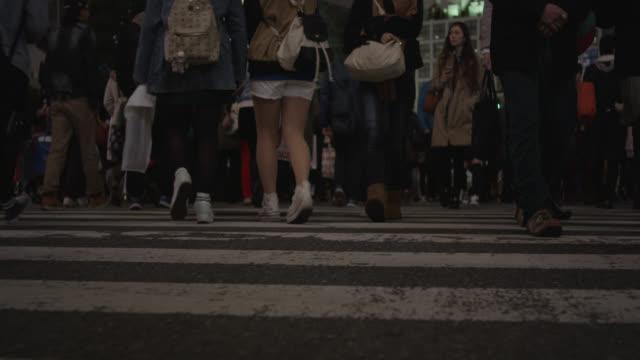 people walk across shibuya crossing in tokyo. - shibuya crossing stock videos & royalty-free footage