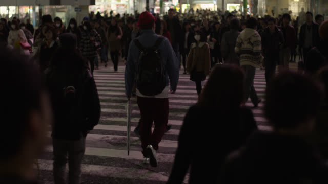 People walk across Shibuya crossing in Tokyo.