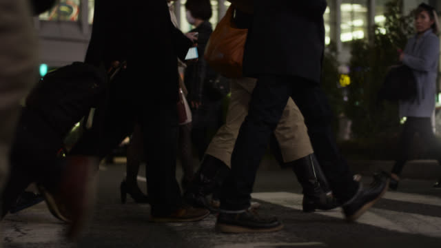 people walk across shibuya crossing in tokyo. - crossing stock videos & royalty-free footage