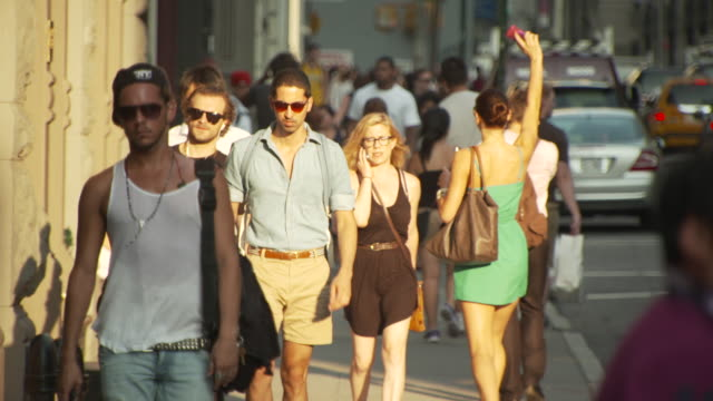 people walk along a busy new york city street in late-afternoon sunlight, usa. - shorts stock-videos und b-roll-filmmaterial