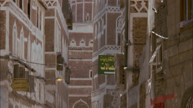 people walk along a narrow street near a minaret. - yemen stock videos & royalty-free footage