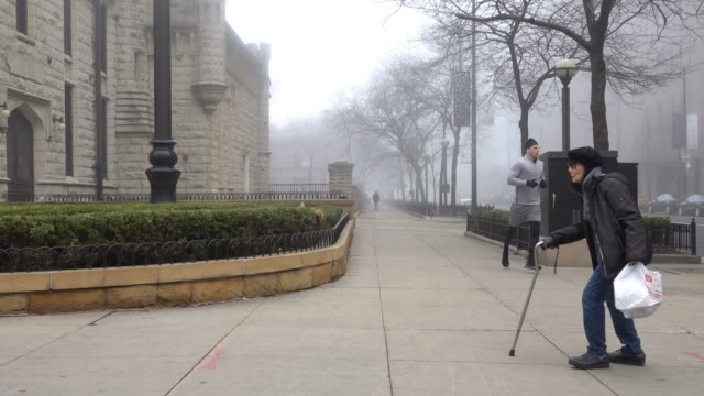 people walk along a nearly-deserted section of michigan avenue known as the magnificent mile on march 27, 2020 in chicago, illinois. nearly all of... - michigan avenue chicago stock videos & royalty-free footage