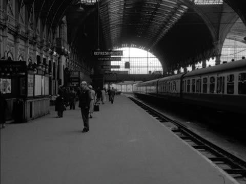 people walk along platform one at paddington railway station. - paddington railway station stock videos & royalty-free footage