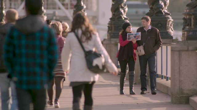 People walk along the Embankment, including two people looking at a tourist guide, central London, UK.