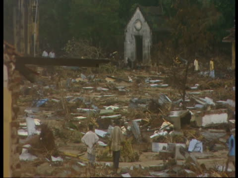 people walk amongst the debris left by the 2004 indian ocean tsunami. - 2004 stock-videos und b-roll-filmmaterial