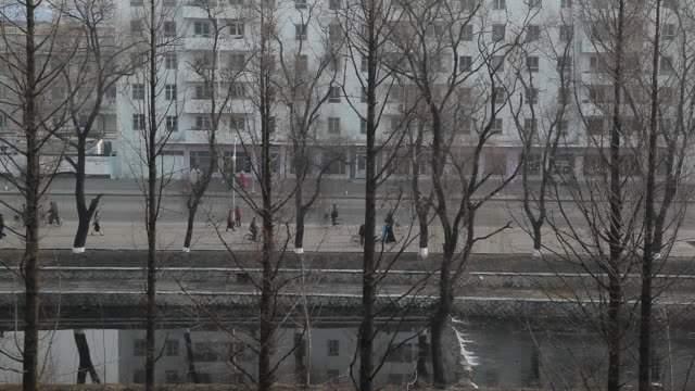 people walk and bike along a canal past a highrise in pyongshong, a satellite city outside of pyongyang, north korea. - pyongyang stock videos and b-roll footage