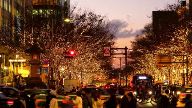 people walk and cars run on aoyama dori street, which street crosses the illuminated omotesando street at sunset at minamiaoyama, minato tokyo japan on december 05 2017. tree lined omotesando street is decorated and illuminated for winter holydays season. - avenue stock videos & royalty-free footage