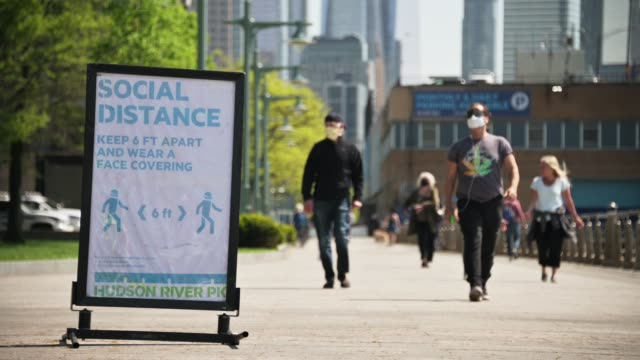 "people walk and exercise near a sign reading ""social distance keep 6 ft apart and wear a face covering"" in hudson river park in the west village... - people stock videos & royalty-free footage"