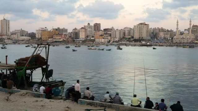 people walk and fish at the port on may 12 2018 in gaza city gaza tensions are high along the gazaisrael border following more than a month of weekly... - 2018 gaza border protests stock videos & royalty-free footage