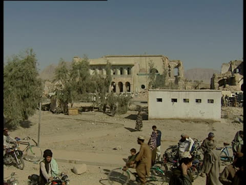 vídeos de stock e filmes b-roll de people walk around an area that has suffered bomb damage afghanistan - kandahar
