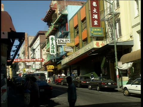 vídeos de stock e filmes b-roll de people walk around chinatown street. chinese signs on side of shops and cars parked either side of road san francisco - san francisco