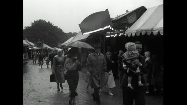people walk around summer fair and tradestands in rain;1951 - 1951 stock videos & royalty-free footage