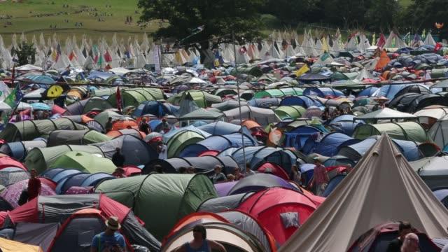 people walk around tents at the glastonbury festival at worthy farm, pilton on june 27, 2015 in glastonbury, england. - day 2 stock videos & royalty-free footage